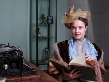 Young Woman In Blue Vintage Dress Late 19th Century Reading The Book In Retro Room