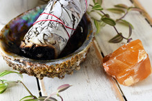 A Close Up Image Of A White Sage Bundle In An Abalone Shell With Honey Calcite On A White Wooden Table Top.