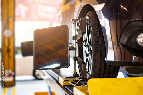 Fototapeta car automobile mechanic working on repairing the wheel tire of vehicle, taking car in for service workshop for male car mechanic fixing problems replacing broken parts of using tools and equipment obraz