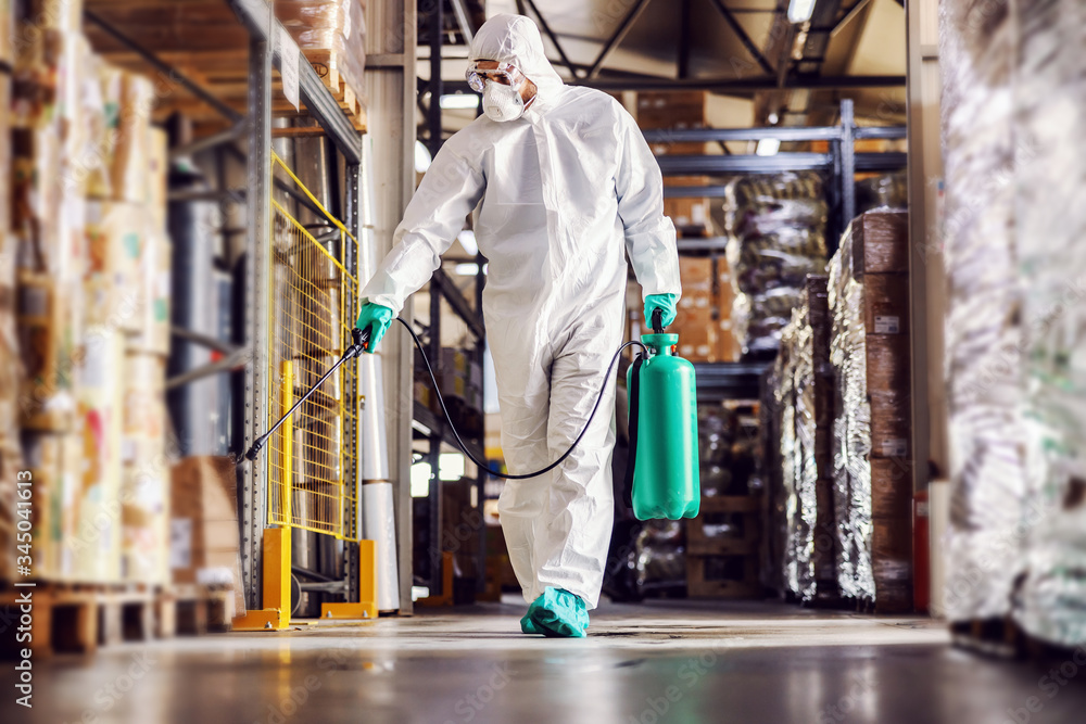 Fototapeta Man in protective suit and mask disinfecting warehouse full of food products from corona virus / covid-19.