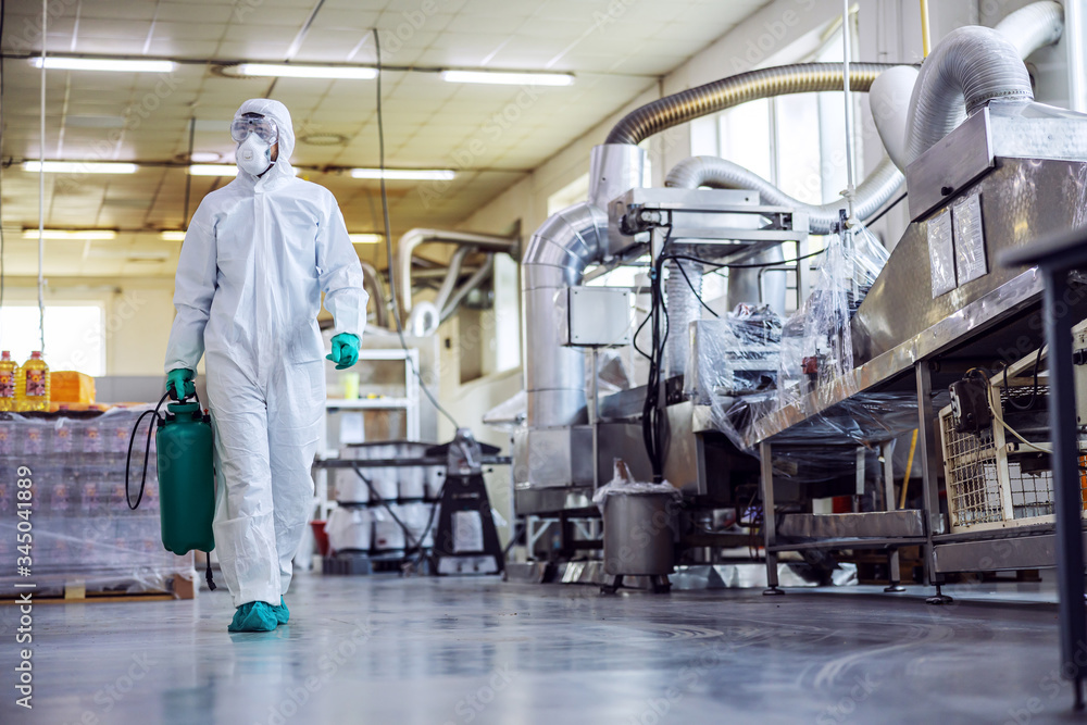 Fototapeta Man in protective suit and mask disinfecting food factory full of food products from corona virus / covid-19.