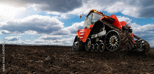 Aufkleber - Rubber tracked agricultural tractor on a field.