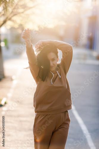 Fotografija dark-haired girl walks around the city and posing in a beige suit