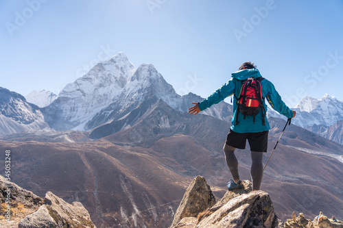 Trail runner standing on top of mountain and looking to Ama Dablam mountain peak Wallpaper Mural