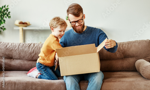 Fototapeta Father and son unpacking delivery box on couch. obraz
