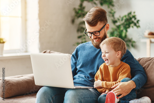 Cuadros en Lienzo Happy father and son using laptop on sofa.