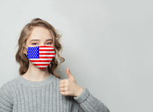 Happy Woman In Face Mask Holding Thumb Up With National Flag USA Background. Flu Epidemic And Virus Protection Concept