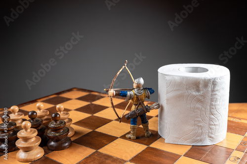 Photo Archer defending a roll of toilet paper from an army of pawns on a chessboard