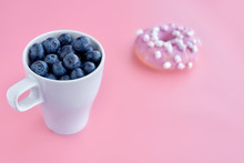 Side View Of A Cup Filled With Blueberries And Donut On Colorful Paper Background. Copy Space. Healthy And Unhealthy Food.Soft Focus
