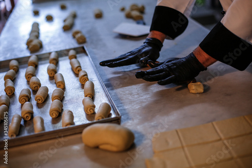 Photo pasticciere con i guanti neri lavora la pasta e prepara dei dolci sul bancone