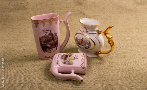 three items from Czech ceramics (Karlovy vary) two of them are pink and the third is white with a gold handle Wallpaper Mural