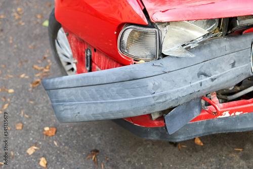 Closeup detail of crashed red car front headlight fender wheel and deformed bumper Fototapeta