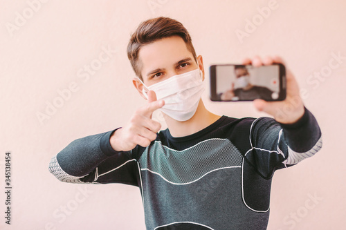Valokuva Confident man fitness coach in medical protective face mask pointing to phone camera for subscribers motivation