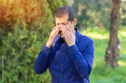 Fototapeta Man covering eyes by hand of bright sunlight obraz