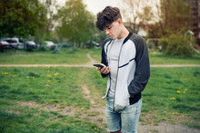 A Teenage Boy Holds A Modern Phone In His Hands And Starts To Call His Parents To Say That Everything Is Fine With Him, Because He Went To A Friend In Another City