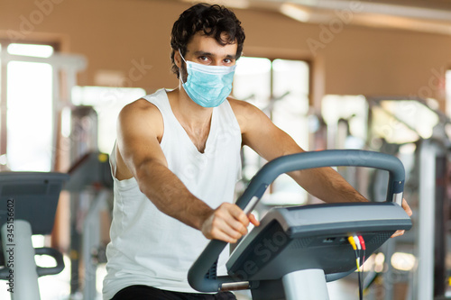 Man in the gym, exercising his legs doing cardio training on bicycle wearing a m Wallpaper Mural