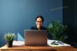 Leinwandbild Motiv Smiling entrepreneur sitting at home working on laptop computer with documents on the table