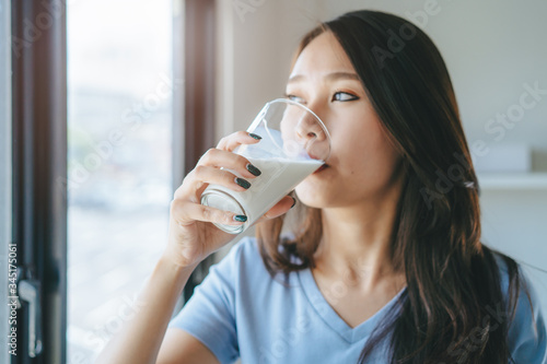 Fotografie, Tablou Close up view of asian woman drinking milk.