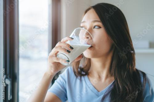Obraz na plátně Close up view of asian woman drinking milk.