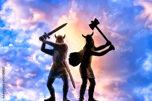 Cuadros en Lienzo Two Viking warriors with sword and double-sided axe against colorful cloudy sky,