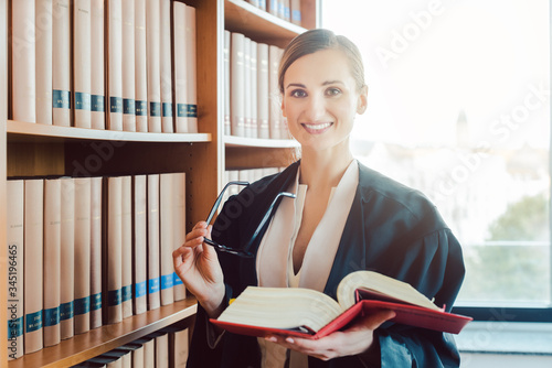 Lawyer working on a difficult case reading in the library Fototapet