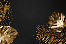 Gold Painted Tropical Leaves On Black Plain Paper Background.