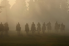 Front Line Of Civil War Soldiers On Horseback With Guns Drawn Moving Forward Toward Battle In The Smokey Haze Of Cannon Fire And Gun Smoke.