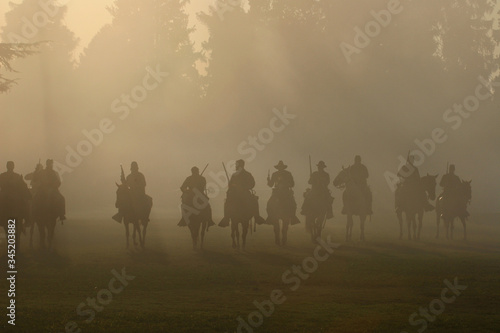 Fotografering Front line of civil war soldiers on horseback with guns drawn moving forward toward battle in the smokey haze of cannon fire and gun smoke