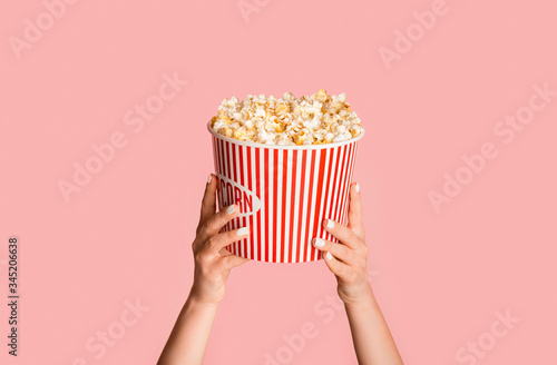 Fototapeta Young girl holding striped bucket with popcorn on pink background, closeup view obraz