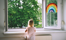 Little Girl Looks Out  Open Wi...