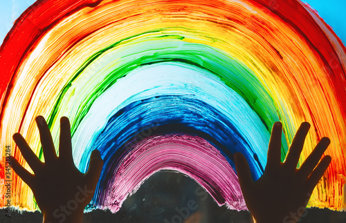 Child hands touch painting rainbow on window.