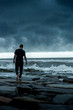 man walking on stormy coast