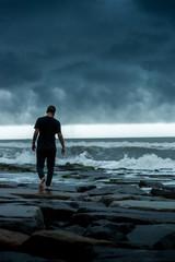 man walking on stormy coast