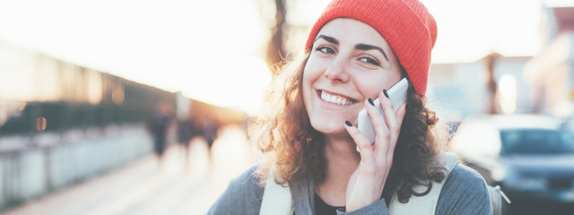 Curly handsome woman talking on the phone on the street, wearing backpack and smiling. Wide screen, panoramic