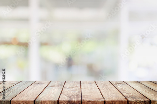 Fototapeta Empty wood table top and blurred coffee shop and restaurant interior background - can used for display or montage your products