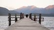 Girl enjoying beautiful sunset on wooden pier, watching mountains in New Zealand.