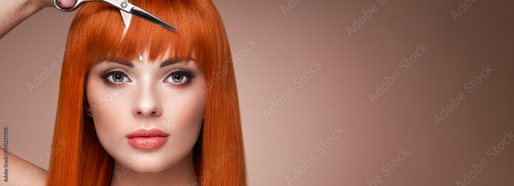 Fototapeta Beautiful young woman with a bright makeup and a smooth long hair holds metal scissors. Model with red hair. Hair salon, haircut. Care and beauty hair products. Perfect make-up