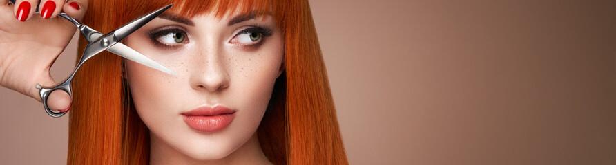 Lijepa mlada žena svijetle šminke i glatke duge kose drži metalne škare. Model s crvenom kosom. Frizerski salon, šišanje. Njega i ljepota proizvodi za kosu. Savršen make-up