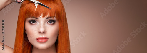 Fotomural Beautiful young woman with a bright makeup and a smooth long hair holds metal scissors