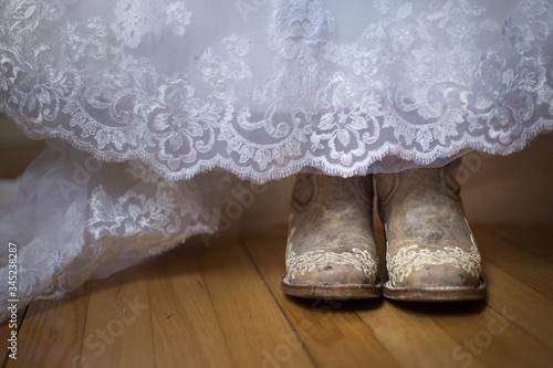 Valokuvatapetti Bride wearing cowboy boots under wedding dress.