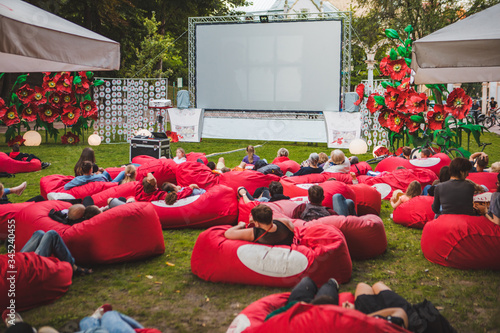 Carta da parati people at city public park watching movie at open air cinema