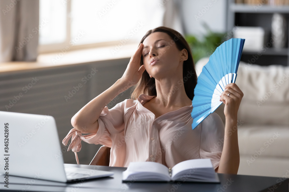 Fototapeta Overheated woman waving fan, sitting at desk with laptop at home, stressed young female suffering from heating at home, feeling discomfort, hot summer weather or fever, heatstroke concept