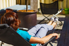 Woman Relaxing In Chair On Ver...