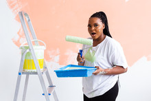Pretty Smiling African American Woman Painting Interior Wall Of Home With Paint Roller. Redecoration, Renovation, Apartment Repair And Refreshment Concept.