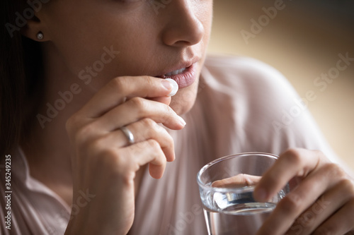 Photo Close up young woman taking white round pill, holding water glass, unhealthy fem