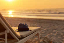 Blue Hat Is Lying On A Chaise Longue On A Beautiful Sandy Beach By The Sea In The Rays Of The Setting Sun. Space For Text