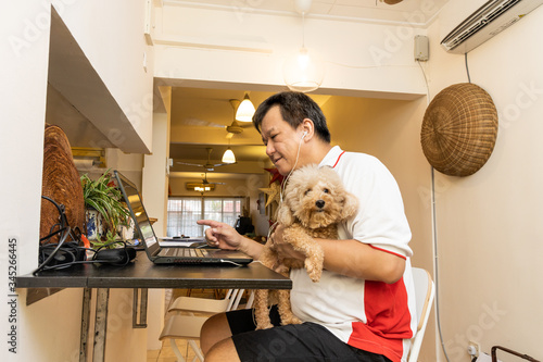 Matured Asian business man work from home accompanied by pet dog during lockdown Wallpaper Mural
