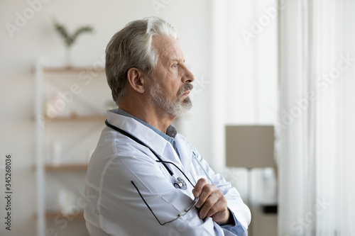 Thoughtful serious senior doctor looking through window lost in thoughts Wallpaper Mural