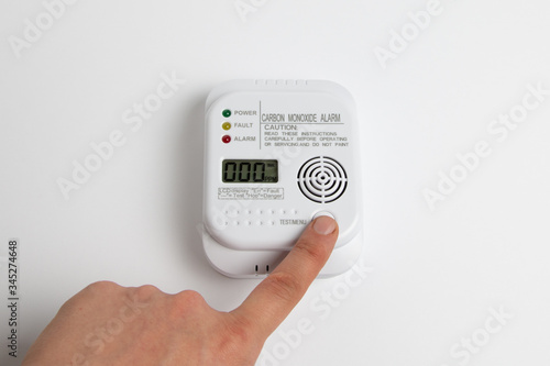 Valokuvatapetti testing carbon monoxide detector on a white wall