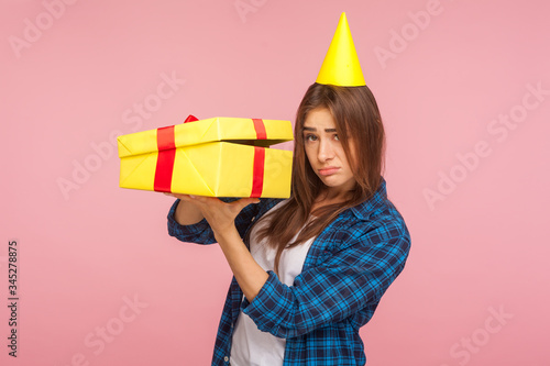 Portrait of unhappy girl with party cone on head holding unwrapped box and looking at camera with disappointed sad expression, dissatisfied with birthday gift Canvas-taulu